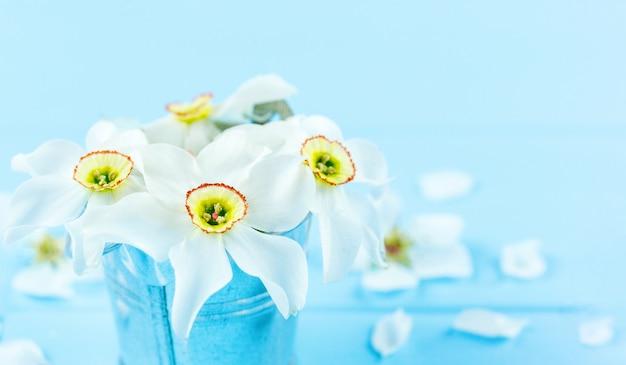 Witte narcissenbloemen in een kleine vaas op decoratieve blauwe achtergrond