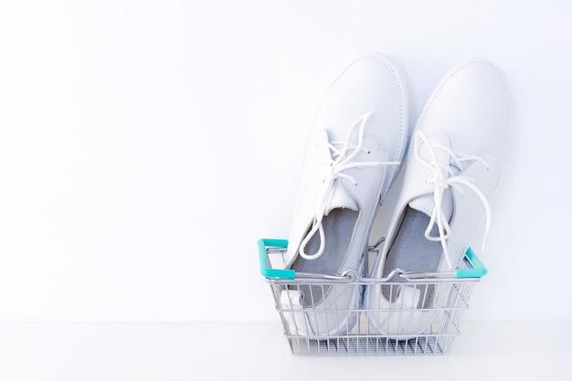 Witte nieuwe sneakers in een winkelmandje op een witte achtergrond.
