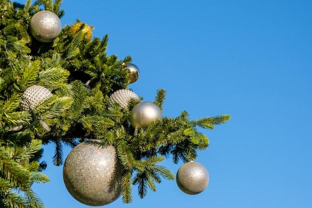 Witte nieuwjaars versieringen en garland op een tak van kunstmatige kerstboom buitenshuis