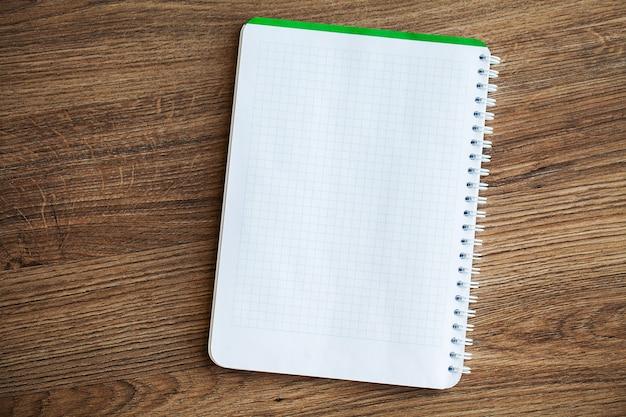 Witte notebook bovenaanzicht op houten tafel.