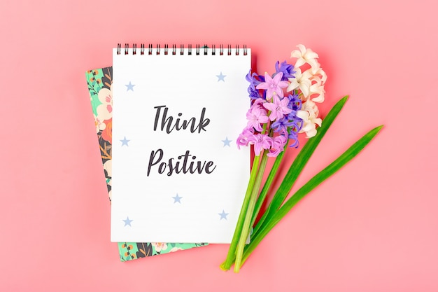 Witte notebook voor notities, boeket van hyacinten bloemen op roze tafel