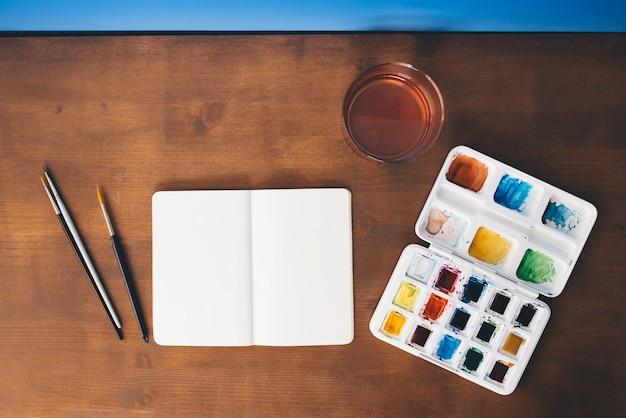 Witte notitieblok openen op een houten tafel met aquarellen en borstels