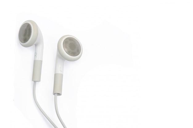 Witte oortelefoons die op witte muur worden geïsoleerd