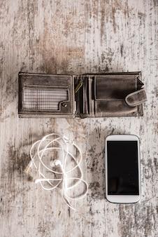 Witte oortelefoons, een portemonnee en een smartphone op een houten tafel.