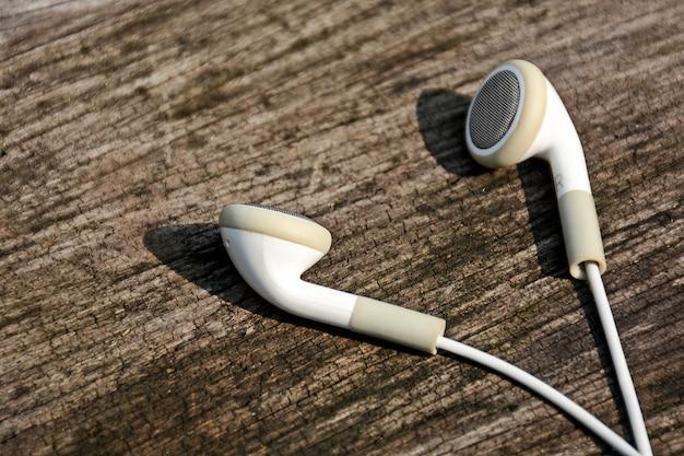 Witte oortelefoons op oude houten achtergrond