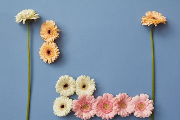 Witte, oranje, roze gerbera op een blauwe achtergrond in de vorm van tetris-beeldjes, conceptspel tetris. creatieve compositie van bloemen. plat leggen.