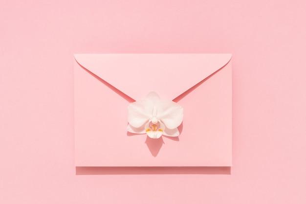 Witte orchideebloem op roze envelop. felicitatiemail voor dames, moederdag, valentijnsdag, verjaardag.