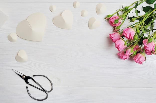 Witte origami harten gemaakt van papier met roze rozen en schaar