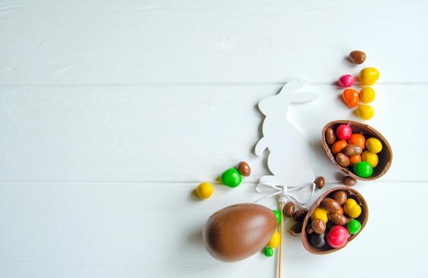 Witte paashaas met chocolade-eieren en snoepjes