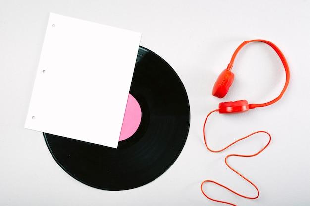 Witte pagina; vinyl record en rode hoofdtelefoon op witte achtergrond