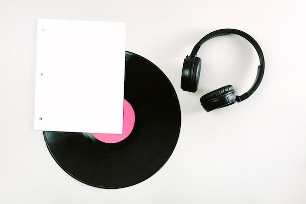 Witte pagina; vinylplaat en hoofdtelefoon op witte achtergrond