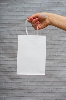 Witte pakket mock-up close-up op een grijze bakstenen achtergrond. wit ecopakket in de hand van een vrouw. online winkelconcept
