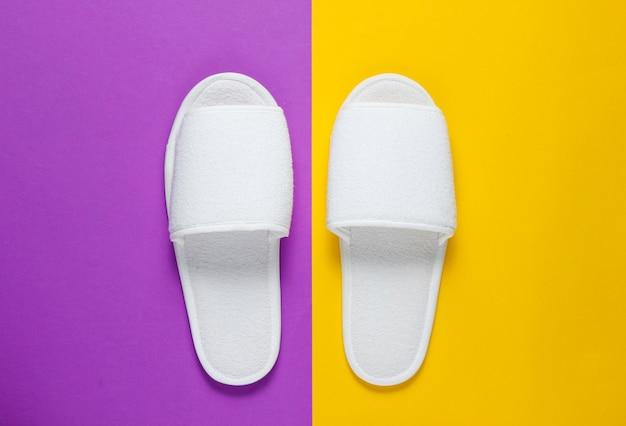 Witte pantoffels op paars en oranje papier