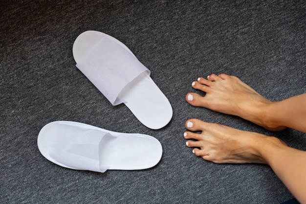 Witte pantoffels op tapijt en vrouwenvoet