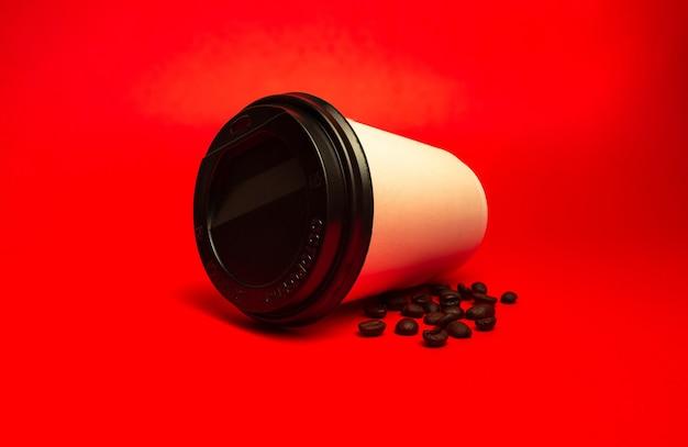 Witte papieren beker met koffiebonen op een rode achtergrond