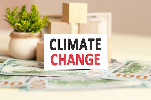 Witte papieren kaart met de tekst climate change staat op het oppervlak van papiergeld, houten blokjes en bloemen