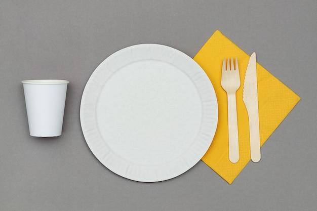 Witte papieren schotel, papieren beker, houten vork en mes op oranje servet op grijze achtergrond, bovenaanzicht. set milieuvriendelijk wegwerpservies van natuurlijk materiaal.