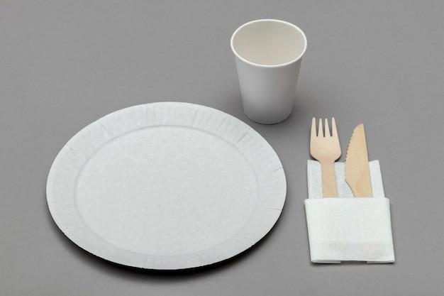 Witte papieren schotel, papieren beker, houten vork en mes op wit servet op grijze achtergrond, perspectief bekijken. set milieuvriendelijk wegwerpservies van natuurlijk materiaal.