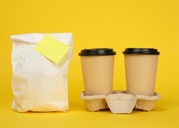 Witte papieren zak, bruine papieren wegwerpbekers met een plastic deksel staan in de lade