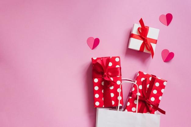Witte papieren zak met geschenkdozen en papieren harten op roze