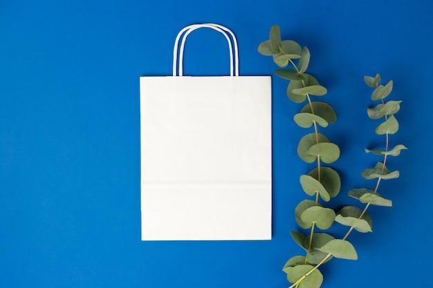 Witte papieren zak met handvatten en eucalyptusbladeren op blauwe achtergrond. platte banner, bovenaanzicht, kopieerruimte, afvalvrij, plasticvrije artikelen. mockup eco-pakket