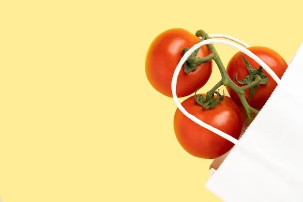 Witte papieren zak met tomaten op gele achtergrond, plaats voor tekst, bovenaanzicht.