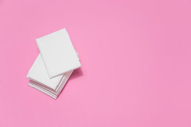 Witte papieren zakdoekjes op donkerroze achtergrond met kopieerruimte