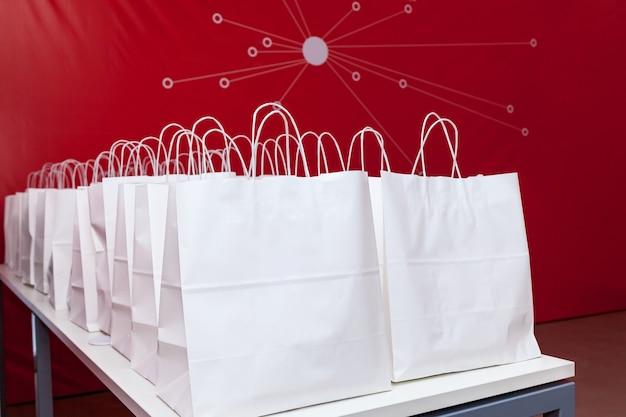 Witte papieren zakken op de witte tafel op de achtergrond van de rode muur. zakken worden in twee gelijke rijen geplaatst.