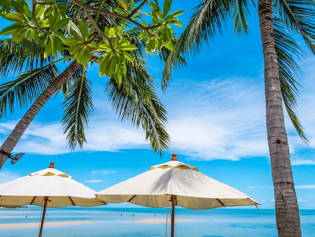 Witte paraplu met kokosnotenpalm met zeeoceaan