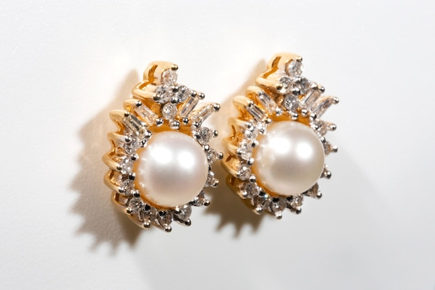 Witte pareloorring met diamanten halo-oorring met stekels in geel goud