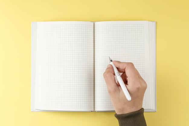 Witte pen in de hand over een opengeslagen notitieboekje