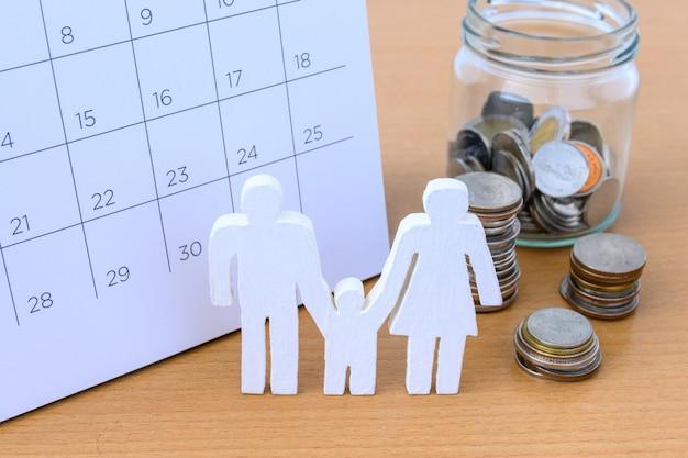 Witte pictogramfamilie en muntstukken op kalender, familieconcept