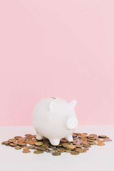 Witte piggybank over de muntstukken die op wit bureau tegen roze achtergrond worden uitgespreid
