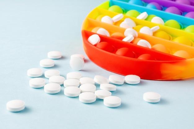 Witte pillen en zintuiglijke speelgoedpoppit op blauwe achtergrond