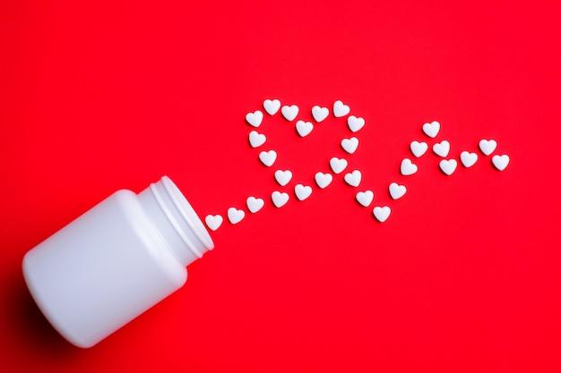 Witte pillen in de vorm van cardiografie in de buurt van witte plastic fles op rode tafel