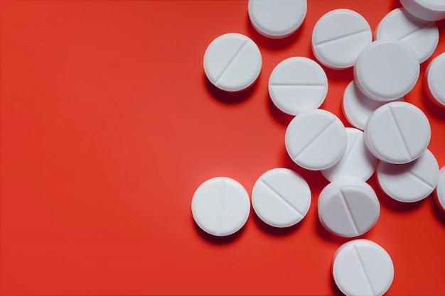 Witte pillen op een rode achtergrond. het concept van geneeskunde, farmacie en gezondheid.