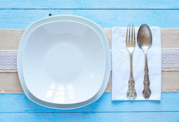 Witte plaat en vork en lepel