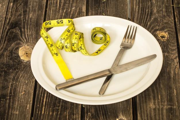 Witte plaat met broodje, gele meetlint en bestek op tafel