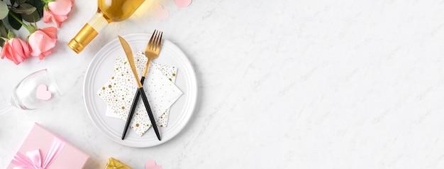 Witte plaat met cadeau en roze roze bloem op marmeren witte tafel achtergrond voor valentijnsdag speciale vakantie dating maaltijd concept.
