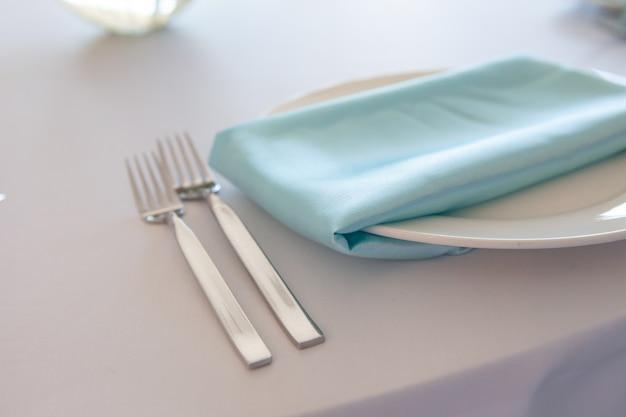 Witte plaat met een turquoise servet, metalen vork en mes, tafel instelling bruiloft