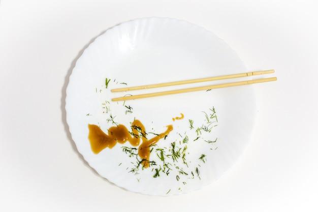 Witte plaat met etensresten en sushi-eetstokjes, gegeten voedsel, bovenaanzicht