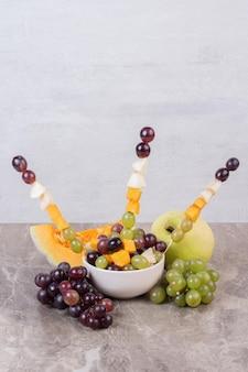 Witte plaat met fruit op marmeren tafel.
