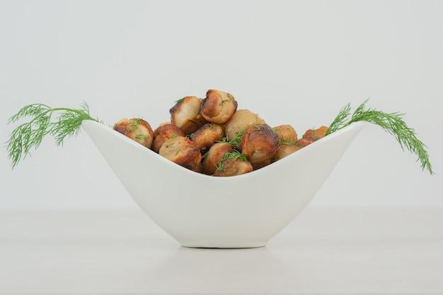 Witte plaat met gebakken aardappel en greens.