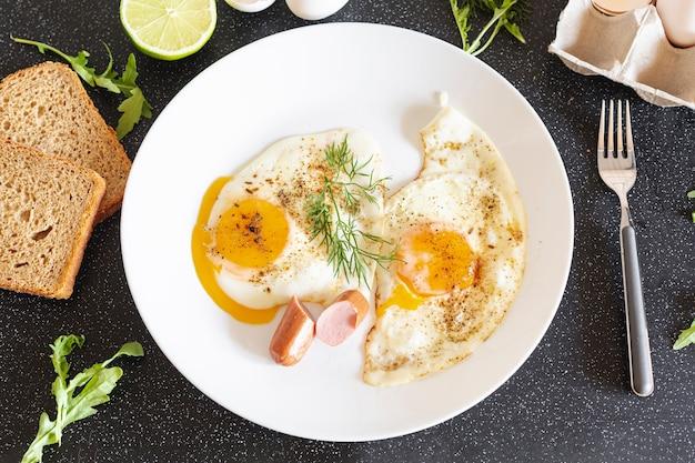 Witte plaat met gebakken eieren en brood op een zwarte tafel