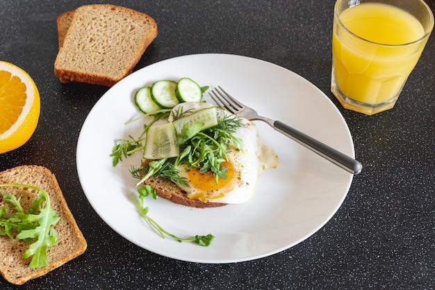 Witte plaat met gebakken eieren en jus d'orange