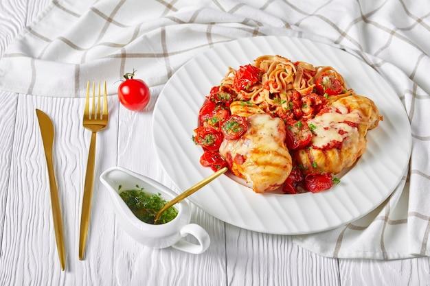 Witte plaat met gegrilde kipfilet, gesmolten mozzarellakaas bovenop, volkoren linguine, kerstomaatjes en knoflookkruidensaus, gouden bestek op een witte houten tafel, close-up