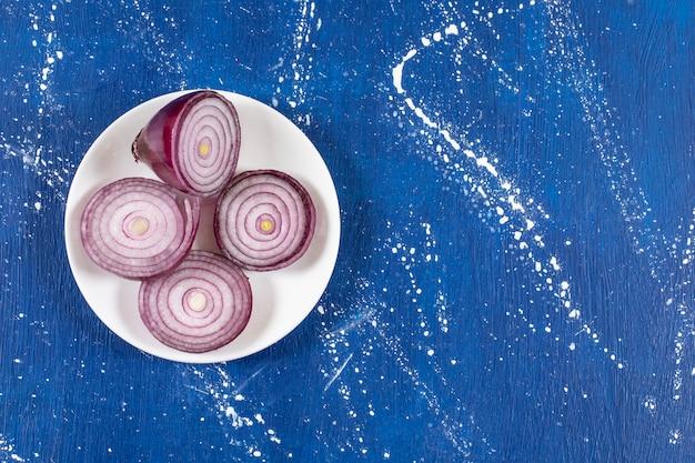 Witte plaat met paarse uienringen op marmeren tafel.