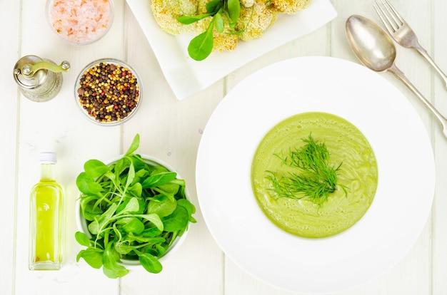 Witte plaat met roomsoep van groene groenten