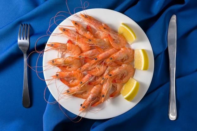 Witte plaat met smakelijke garnalen met citroen geserveerd op blauw met mes en vork. bovenaanzicht