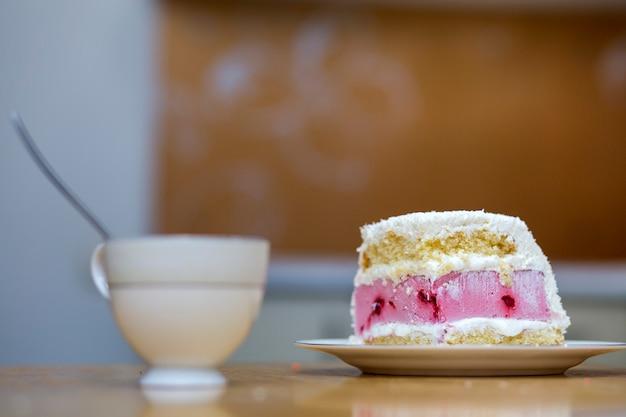 Witte plaat met verse heerlijke lekker zelfgemaakte stuk fruit koekje witte en roze romige cake op keukentafel op porseleinen beker op licht wazig kopie ruimte